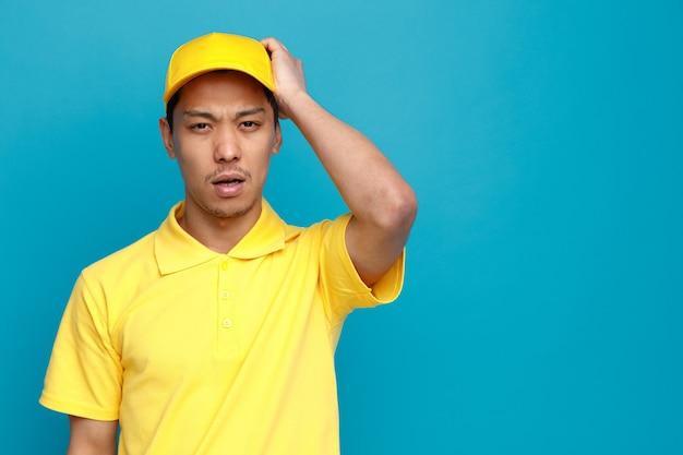 Сожалеющий молодой доставщик в униформе и кепке, держащий руку на голове