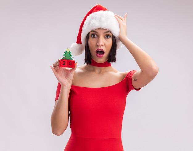 흰색 배경에 고립 된 머리에 손을 유지 카메라를보고 날짜와 크리스마스 트리 장난감을 들고 산타 모자를 쓰고 어린 소녀를 애타게