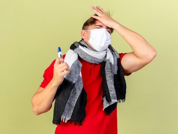 オリーブグリーンの壁に隔離された目を閉じて頭に手を保持している温度計を保持しているマスクとスカーフを身に着けている若いハンサムな金髪の病気の男を後悔
