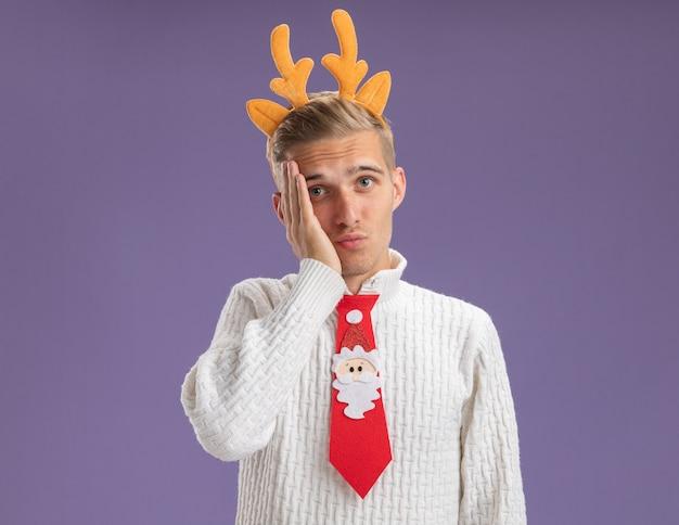 Rammarico giovane bel ragazzo che indossa la fascia di corna di renna e cravatta di babbo natale che guarda l'obbiettivo tenendo la mano sul viso isolato su sfondo viola con spazio di copia