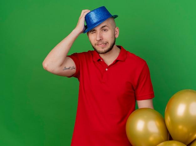 한 눈으로 머리에 손을 넣어 측면을보고 풍선 근처에 서있는 파티 모자를 쓰고 젊은 잘 생긴 슬라브 파티 사람을 유감스럽게 생각하고 복사 공간이 녹색 배경에 고립 폐쇄
