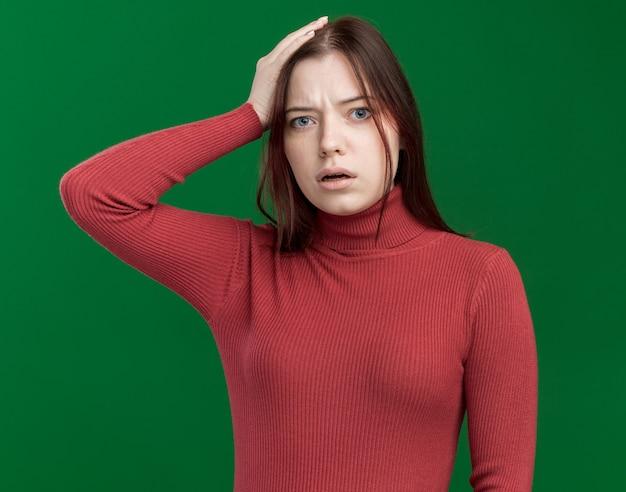 Rimpiangendo la giovane bella ragazza che mette la mano sulla testa isolata sul muro verde