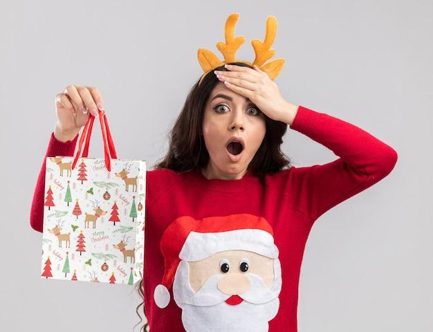 Сожалеющая молодая красивая девушка в повязке на голову из оленьих рогов и свитере санта-клауса, держащая рождественский подарочный пакет, глядя, держа руку на лбу