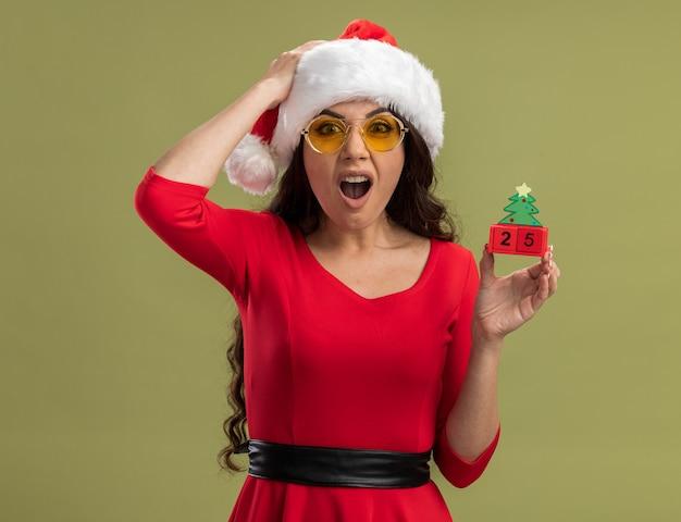 Сожаление о молодой красивой девушке в шляпе санта-клауса и очках, держащей елочную игрушку с датой, держащей руку на голове, изолированной на оливково-зеленой стене