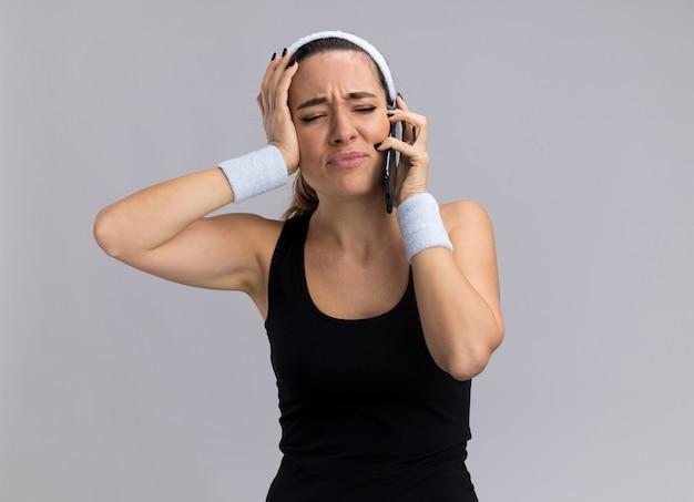 Сожаление о молодой красивой спортивной девушке с повязкой на голову и браслетах, говорящей по телефону, смотрящей в сторону, держащей руку на голове, изолированной на белой стене с копией пространства