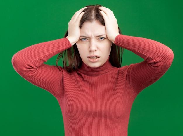 녹색 벽에 격리된 머리에 손을 얹고 앞을 바라보는 유감스러운 젊은 예쁜 여자