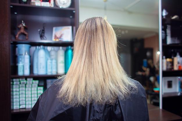 끝이 갈라진 머리카락을 다시 자라십시오. 여자는 미용사에게 와서 염색을하고 머리를 자른다.