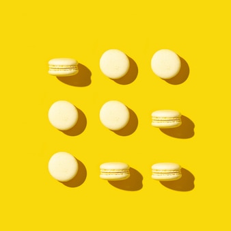 밝은 노란색 쿠키 마카롱의 규칙적인 창의적인 패턴. 흑백 인사말 카드