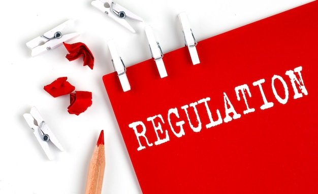 Regulation text on red paper with office tools on the white background