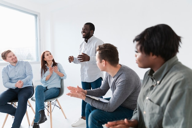 Rehab patients applauding afro-american man