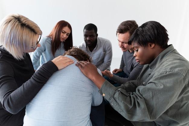 Rehab patients consoling a sad man