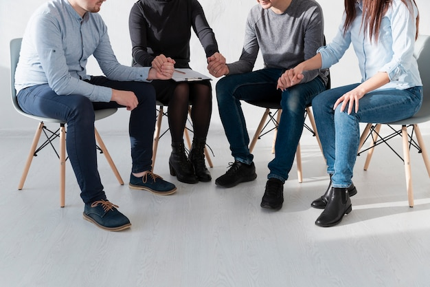 Rehab patients sitting on chairs and holding hands