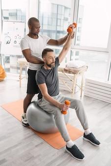재활 활동. 그의 트레이너와 함께 운동하는 동안 의대 공에 앉아 똑똑한 좋은 사람
