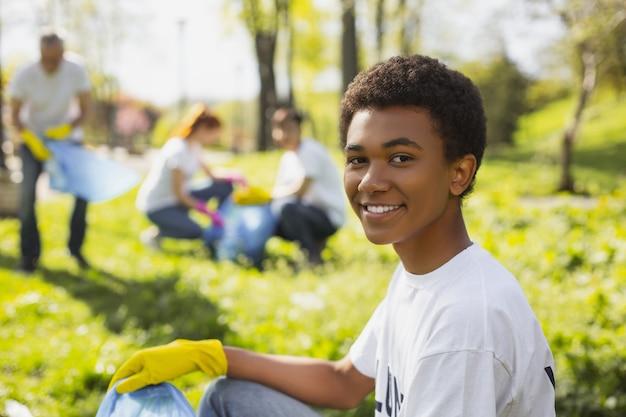 Реабилитация природы. афро-американский волонтер мужского пола смотрит в камеру во время сбора помета