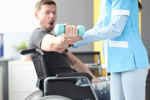 Rehabilitation physician helping lift dumbbell to patient in wheelchair. medical rehabilitation of disabled people concept