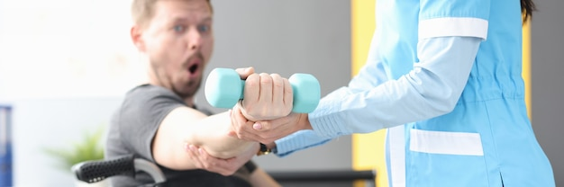 Rehabilitation physician helping lift dumbbell to patient in wheelchair medical rehabilitation