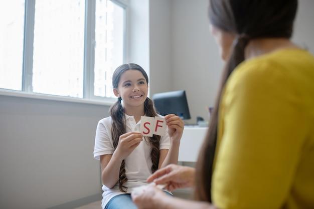 재활, 심리학자. 알파벳 카드와 아동 심리학자를 들고 긴 검은 머리를 가진 웃는 학령기 소녀