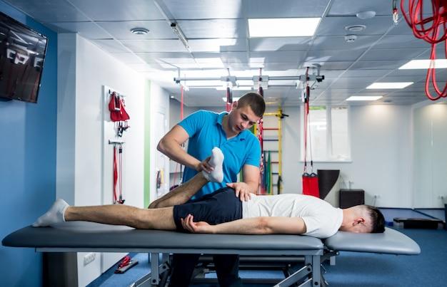 재활 요법. 재활 센터에서 젊은 남성 환자와 함께 일하는 물리 치료사