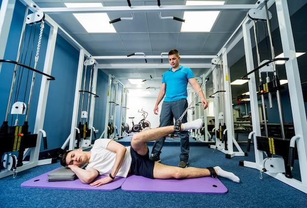 재활 요법. 물리 치료사의 감독하에 매트에 운동을하는 젊은 남자.