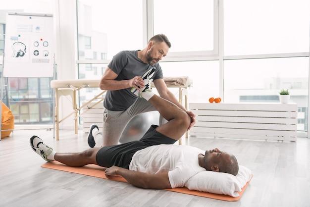 リハビリ訓練。彼と一緒に運動しながら患者の上に立っているスマートな強いトレーナー
