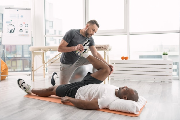 Rehabilitation training. smart strong trainer standing above the patient while working out with him