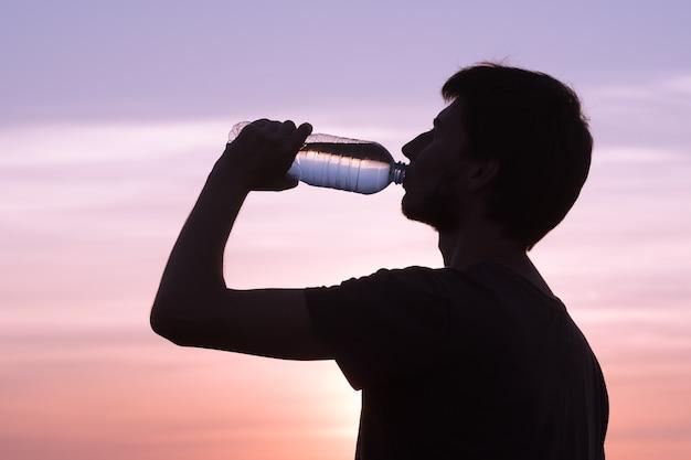 体に水分を補給します。水のボトルを飲む男性。