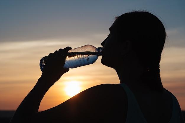 体に水分を補給します。晴れた日に屋外で水を飲むスポーティな女性。