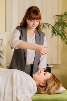 Reiki healer cleans the patient's chakras