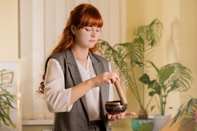 Целитель рейки использует поющую чашу, чтобы лечить пациента