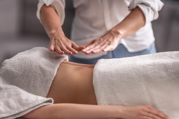 여성 고객의 가슴과 복부 위로 양손을 잡고 있는 치료사와 함께 여성 환자에 대한 레이키 요법.