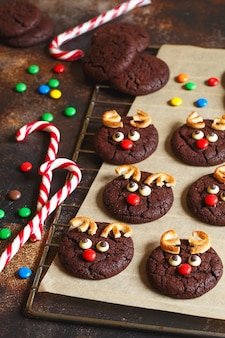 Reindeer cookies with candy red nose on a baking paper