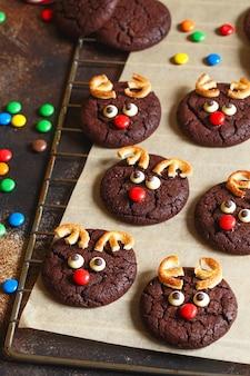 ベーキングペーパーにキャンディーの赤い鼻を持つトナカイのクッキー