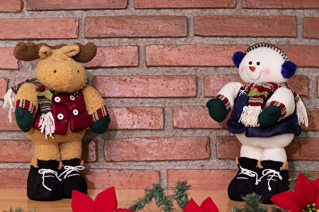 A reindeer and a plush snowman with a scarf and gloves, in front of a brick background on a wood