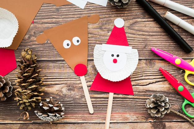 Reindeer and santa claus prop with paper; pinecone; scissor and felt-tip pen on wooden desk
