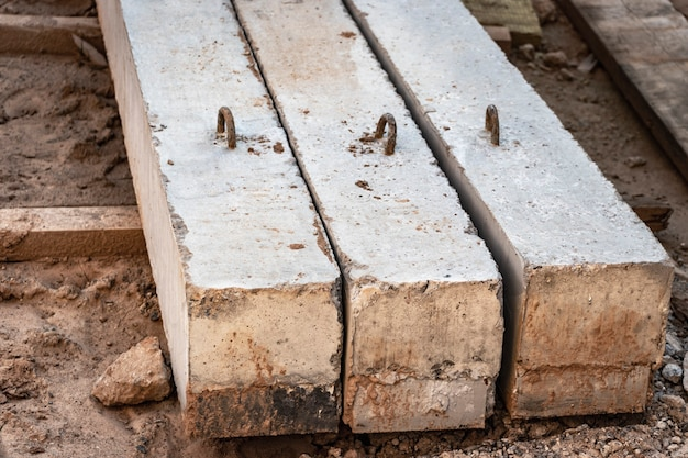 Reinforced concrete beams for building structures stacked at a construction site.