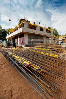 Усиленный каркас на переднем плане строящегося нового монолитного дома на фоне голубого неба