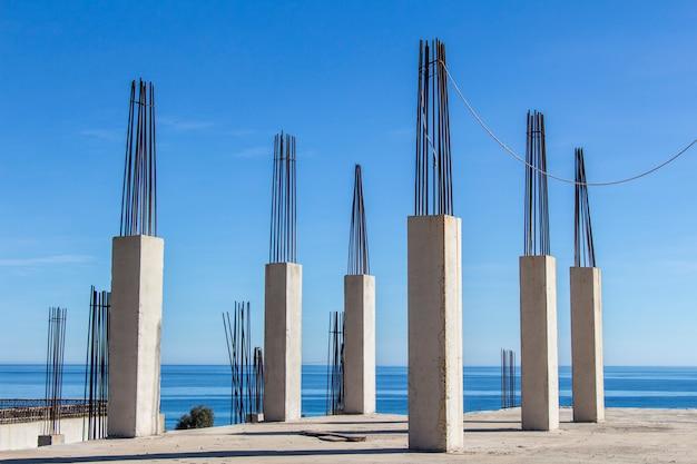 鉄筋の取り付け、背景に海のあるコンクリート柱、コンクリート型枠