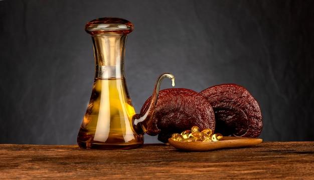 Reishi or lingzhi mushroom and oil on black background.