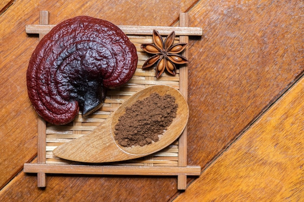 Reishi or lingzhi mushroom and powder on an old wood. top view