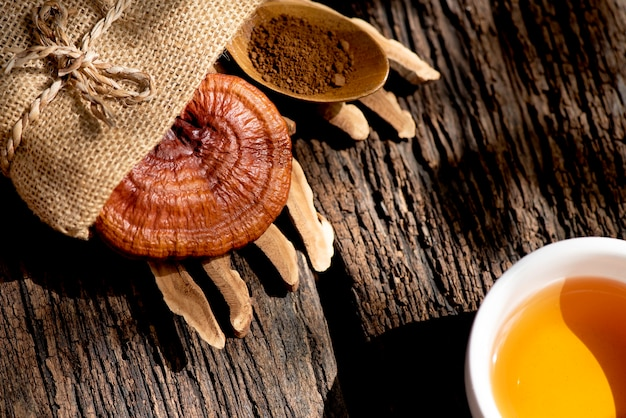 Reishi or lingzhi mushroom and tea on an old wooden.
