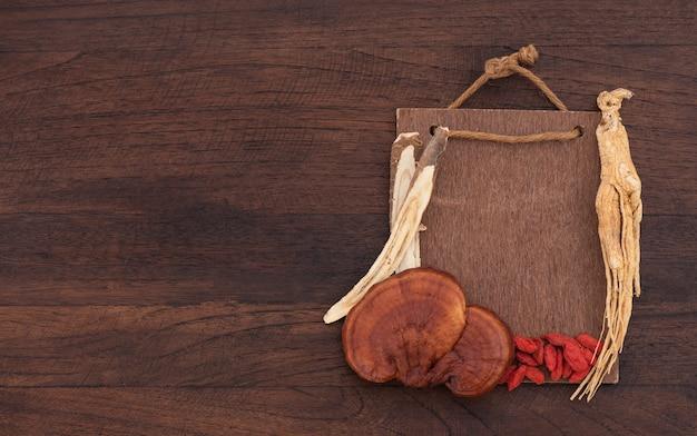 Reishi 또는 lingzhi 버섯, 인삼, 구기자 열매 씨앗 및 감초 나무는 오래된 나무 표면에 있습니다. 평면도, 평면 위치.