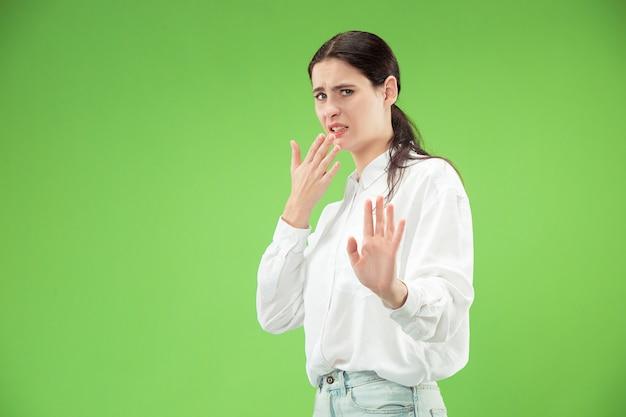 Отклонение, отказ, концепция сомнения. сомнительная женщина с продуманным выражением лица, делающая выбор. молодая эмоциональная женщина. человеческие эмоции, концепция выражения лица. студия. изолированные на модном зеленом