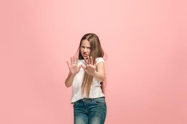 Отклонение, отказ, концепция сомнения. молодая эмоциональная девочка-подросток в студии, отвергая что-то против розового