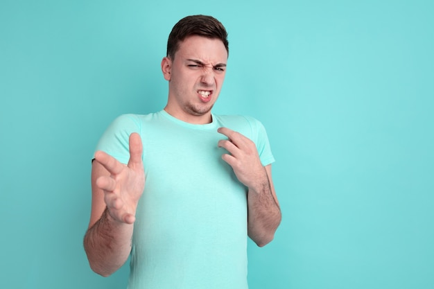 Rejecting, disguasted. caucasian young man's portrait isolated on blue  wall. beautiful male model in casual style, pastel colors. concept of human emotions, facial expression
