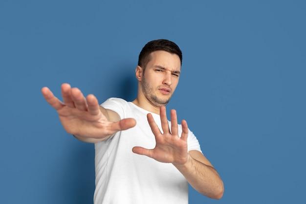 Отвергая, замаскированный. портрет кавказского молодого человека, изолированные на синей стене студии.