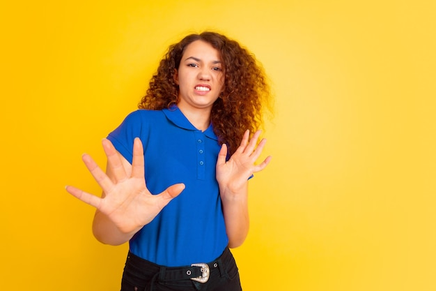 拒絶、不信感。黄色のスタジオの背景に白人の 10 代の少女の肖像画。シャツを着た美しい女性の巻き毛モデル。人間の感情、表情、販売、広告、教育のコンセプト。コピースペース。