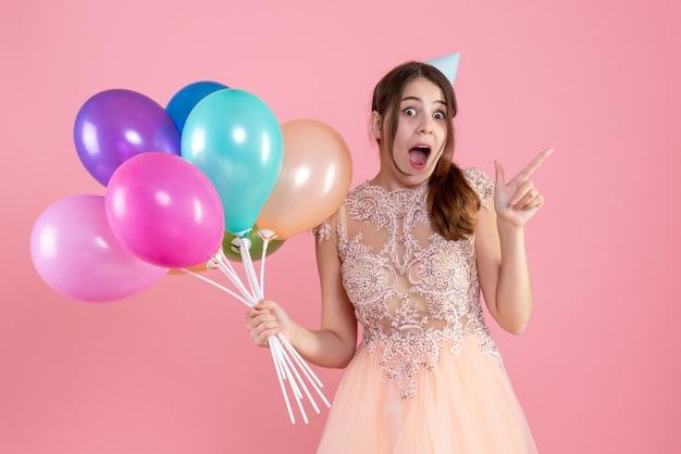핑크에 풍선을 들고 파티 모자와 함께 기뻐 소녀