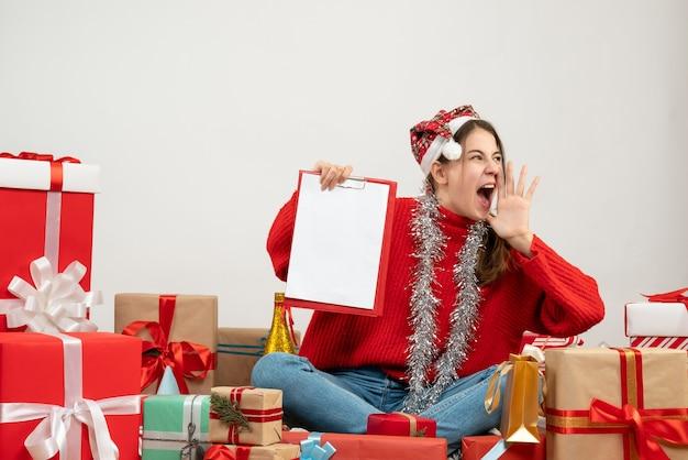 ファイルを保持し、白いプレゼントの周りに座って叫んでサンタの帽子をかぶって喜んだ女の子