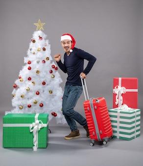 Gioì giovane che va con la valigia rossa sul grigio