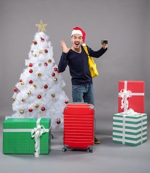 카드와 크리스마스 트리 근처에 서있는 노란색 배낭과 함께 기뻐 젊은 남자와 회색 선물